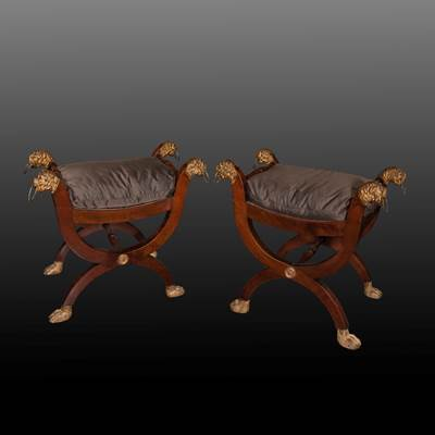 A pair of curule mahogany stools, decoration of lions heads, Italy, early 19th century (62 cm wide, 58 cm high, 49 cm seating height, 41 cm deep)