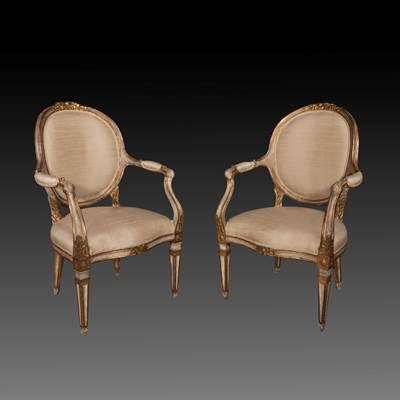 Exceptionnelle paire de fauteuils en bois laqué ivoire et doré, finement sculptés de fleurs et rinceaux, dossiers ovales, accotoirs mouvementés, pieds tronconiques, Turin, Italie, vers 1770 (hauteur 103 cm, largeur 67 cm, profondeur 62 cm)